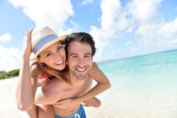 Man giving piggyback ride to girlfriend on Caribbean beach