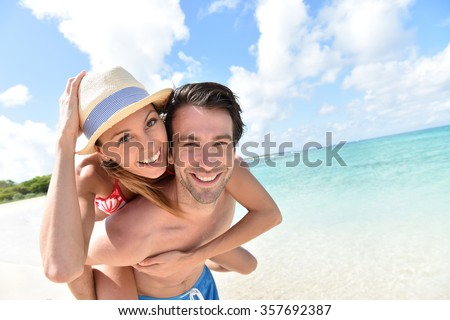 Man giving piggyback ride to girlfriend on Caribbean beach #357692387