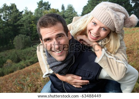 Man giving piggyback ride to smiling blond woman