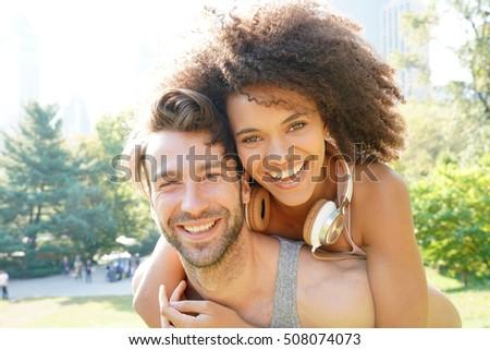 man giving piggyback ride to...