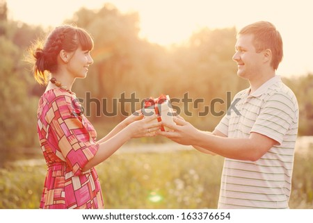 Man giving to his woman a gift box Happy middle-aged couple in love outdoors in the sunlight at sunset Love concept Retro style