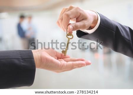 Man giving women a  golden key in office