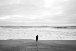 Man goes to the sea on dark sand beach under cloudy sky