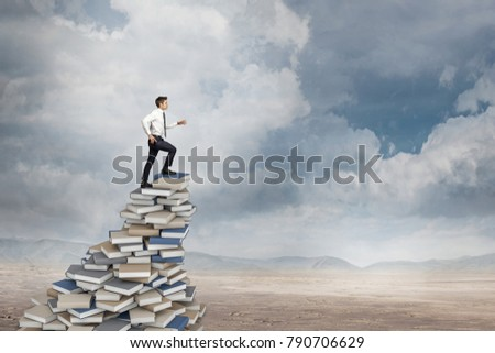 man goes up on books pile in the desert wisdom concept #790706629