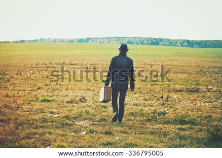 man going with suitcase in field. Concept freedom, loneliness or traveling concept