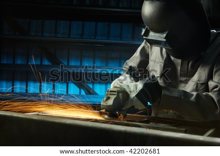 man grinding in workshop with safety precaution