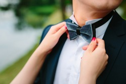 Man groom in wedding suit with bow tie. Hands bride, care, fix, adjust, fashion