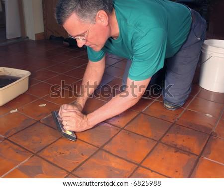 Man grouting ceramic tile - stock photo
