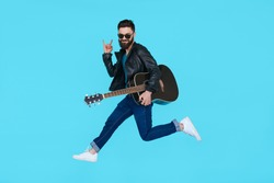 Man guitar player jumps while showing rock gesture on blue background. Isolated in motion