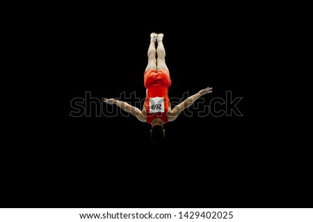 man gymnast flying in air somersault exercise on black background #1429402025