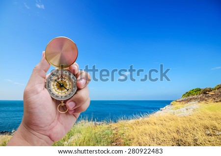 Man hand and compass with Wide angle view on seascape background