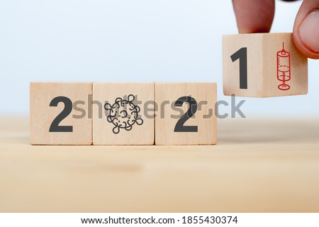 Photo of  man hand arranging on wooden cube from 2020 which covid-19 spread to 2021 years which hope to found vaccine of corona virus with the sunset ,sunrise background. Happy health new year 2021 concept