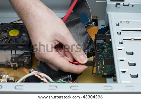 Man hand  assembles computer cable into system unit