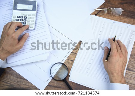 man hand calculator and documant with magnifier on table