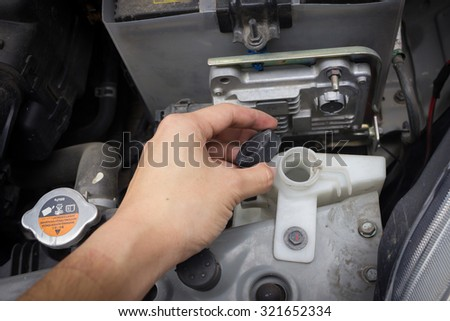man hand check and fill water in cooling system Thailand Eco Car 1600cc with open hood show parts in side. #321652334