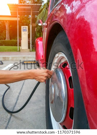 Man hand checking pressure and filling air in tire of red car.