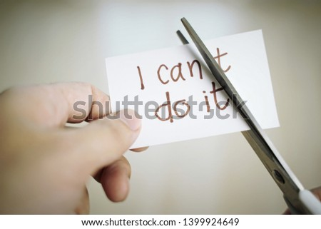 Man hand cutting paper note with scissors to remove T word from I can't do it texts. Positive attitude, self belief and motivation concept. #1399924649