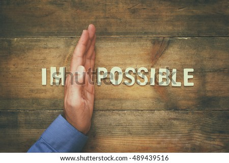 man hand dividing the letters IM from the word impossible so it says possible. #489439516
