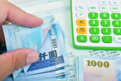 Man hand during counting banknote Taiwan dollar bills.Business concept