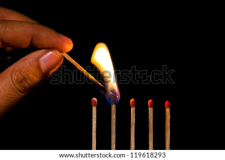 Man hand fire a row of matches on black background