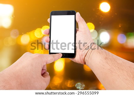 Man hand hold blank touch screen smart phone on abstract blurred bokeh of night light background.