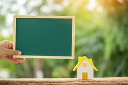 Man hand hold the blackboard with announce and offer for sale the  house model put on the wood on sunlight in the public park, Loan for business investment sell the real estate or buy home concept.