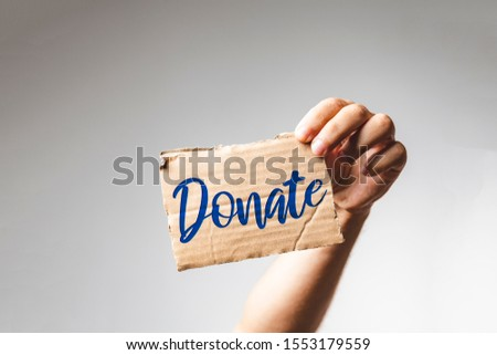 man hand holding a cardboard with the text donate against white background - Charity Concept