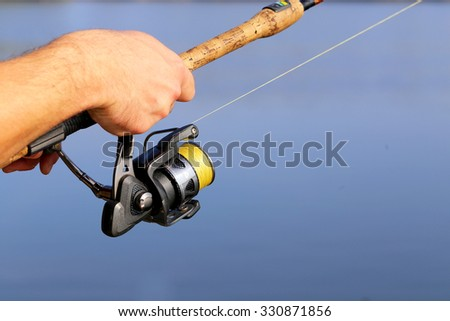 man hand holding a fishing rod and reel #330871856