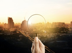 Man hand holding a magnifying glass, The cityscape in focus on background, business vision