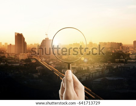Man hand holding a magnifying glass, The cityscape in focus on background, business vision #641713729