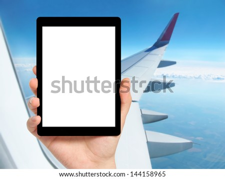 man hand holding a tablet computer with isolated screen against the background of the window with blue sky and airplane wing
