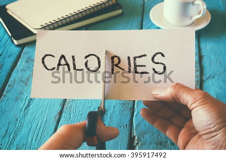 man hand holding card with the word calories. cutting calories and costs concept. retro style image