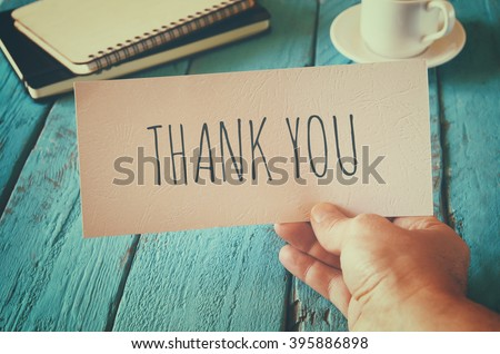 Photo of  man hand holding card with the word thank you. retro style image