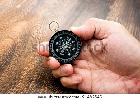 Man Hand Holding Chrome Compass on top of a Wooden Texture Table with space for text