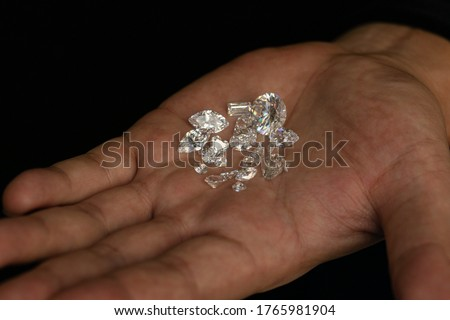 Man hand holding cut and polished diamonds. Loose diamond in hands. Fancy shape brilliant. Model diamond on black background. Top color diamond.