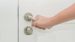 Man hand holding door element handle for open or lock the door.
