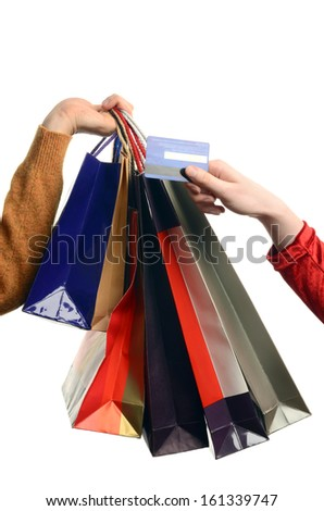 Man hand holding many shopping bags, female hand holding a credit card. Hand of a man with shopping bags woman paying with credit card.  Isolated on white. - stock photo