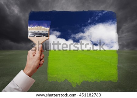 Man hand holding painting brush, paint bright day with blue sky and white cloud on green grass field replace bad cloudy day. Conceptual illustration of new better world or optimistic vision.