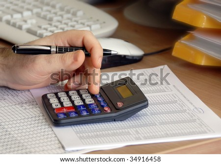 man hand holding pen on calculator buttons in office