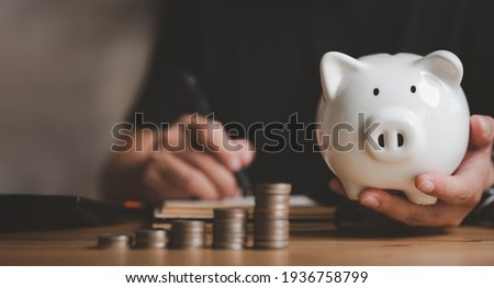Man hand holding piggy bank on wood table, saving money wealth and financial concept, Business, finance, investment, Financial planning.