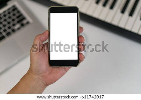 Man hand holding smart phone with white blank screen on blur electric piano keyboard and computer keyboard #611742017