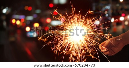 Man hand holding sparkler or firework on street night background #670284793