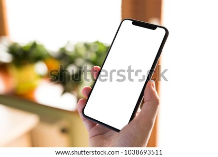 Man hand holding the black smartphone with big blank screen and modern frame less design in home interior, living room - isolated on white background angled position #1038693511