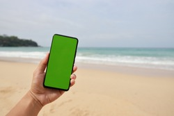 Man hand holding the smartphone with green screen isolated on the beach background.