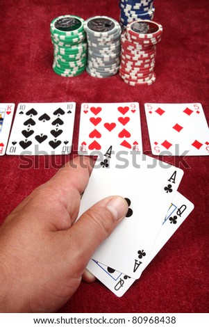 Man hand holding two cards in a game of poker