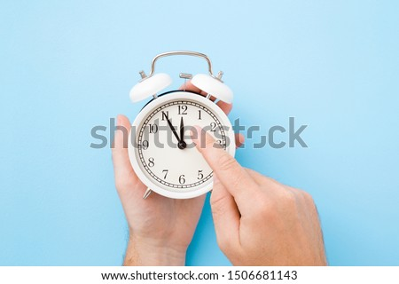 Man hand holding white alarm clock. Finger pointing to arrow of twelve o'clock. Light pastel blue background. Time change concept. Closeup.