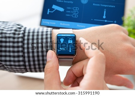 man hand in watch with program smart home on the screen against the background of computer