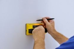 Man hand is scanning wall by uses Multi-Sense Technology to find studs more accurately through difficult surfaces. soft focus