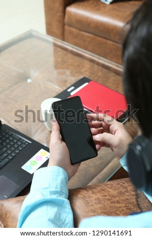Man hand is using phone and listening music with headphone.