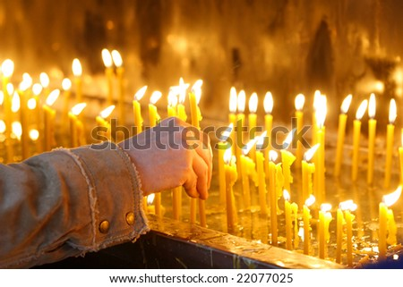 man hand lighting candles  in a church